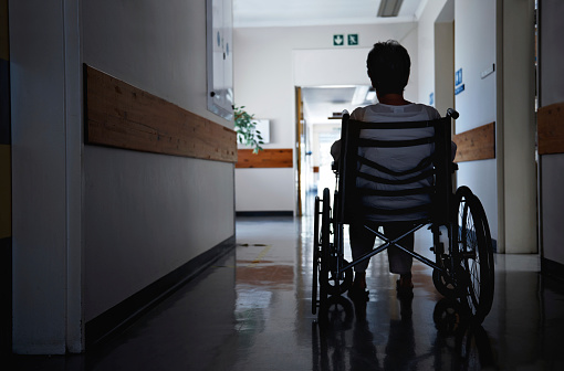 Rearview shot of a senior woman sitting in a wheelchair unattended in a nursing home hallway