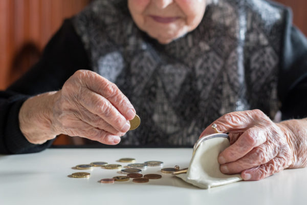 Elderly woman sits at a table, counting coins