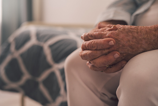 Cropped shot of a senior woman sitting with her hands clasped in a nursing home